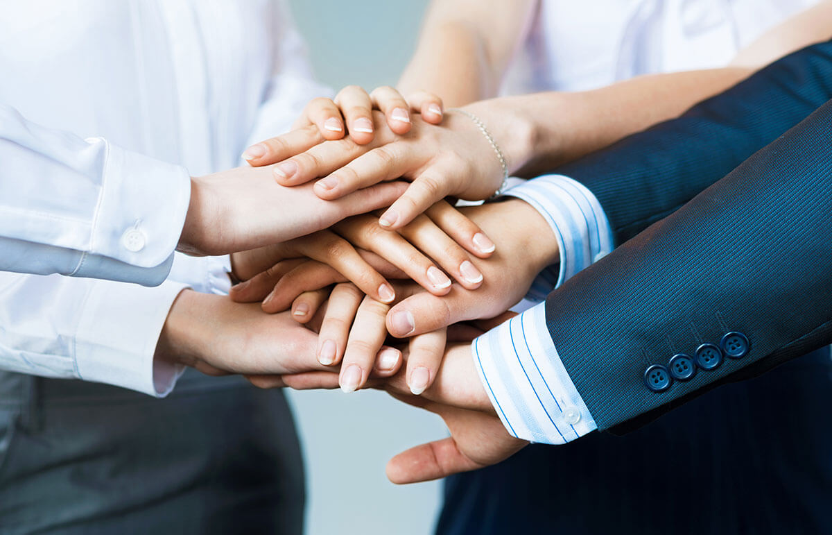 Group of business people putting their hands together.