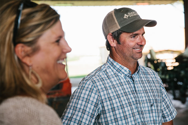 Man wearing Farm Credit Midsouth hat and woman smiling at the camera.