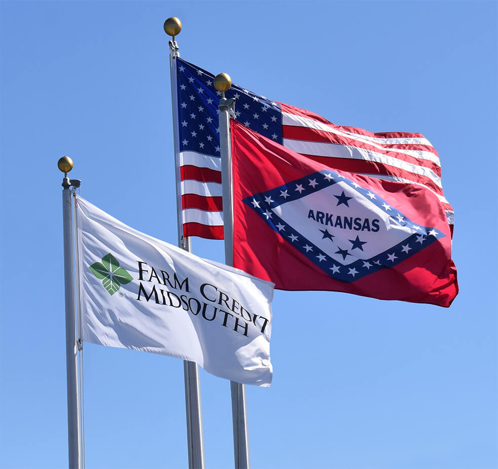 US, Arkansas, and Farm Credit Midsouth Flags blowingin the wind.