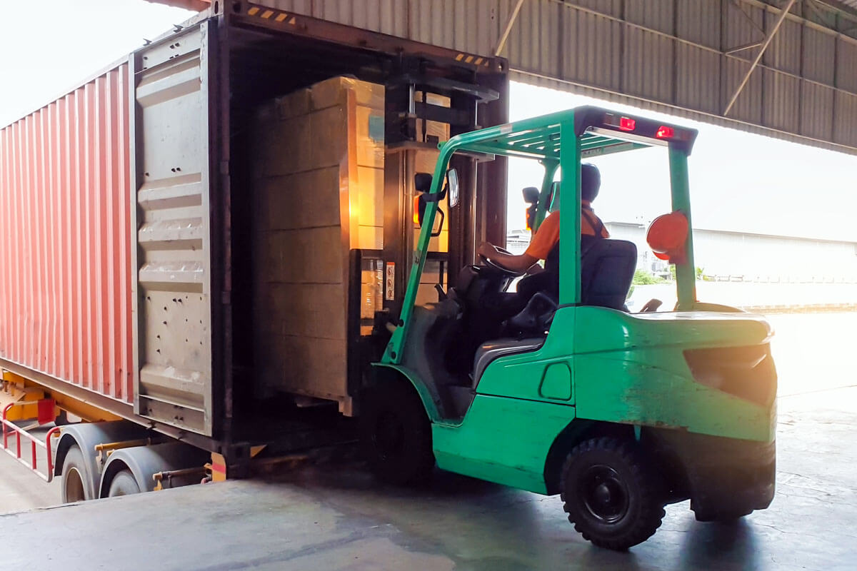A pallet being loaded into a container by a forklift