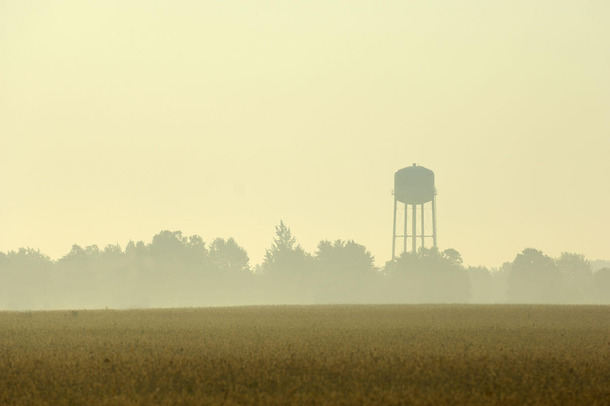 A dusty farm with a water tower in the background