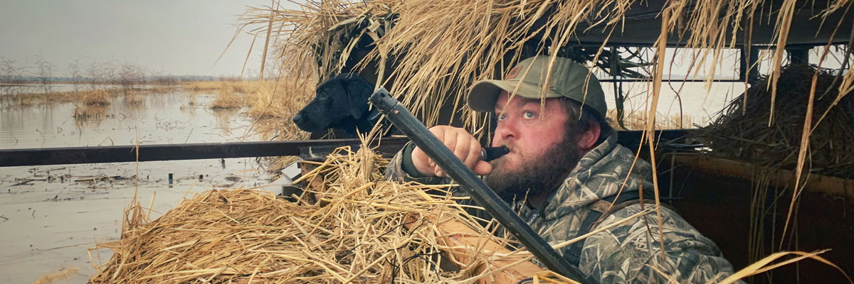 A hunter and his lab in a duck blind calling ducks