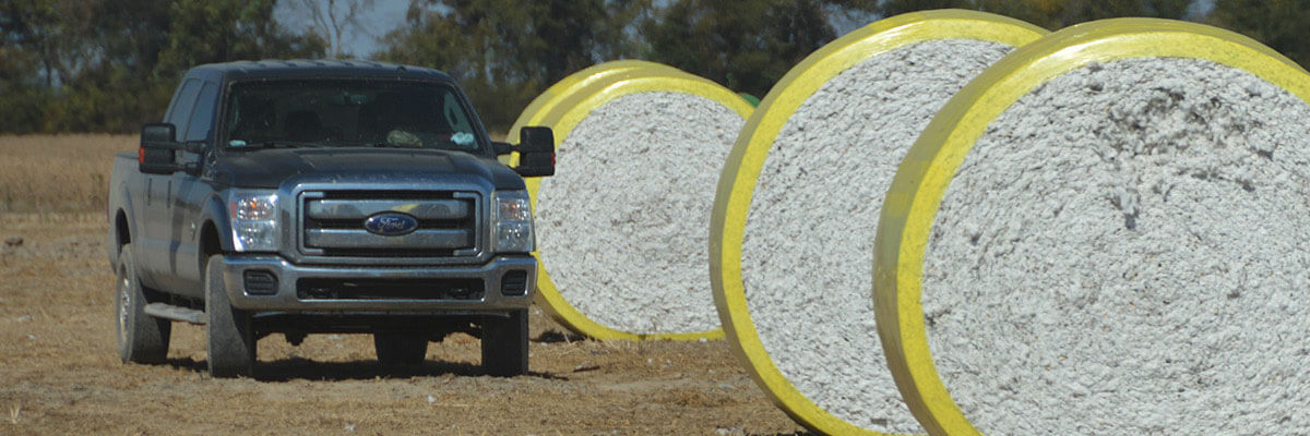 A pickup truck next to some rolls of cotton