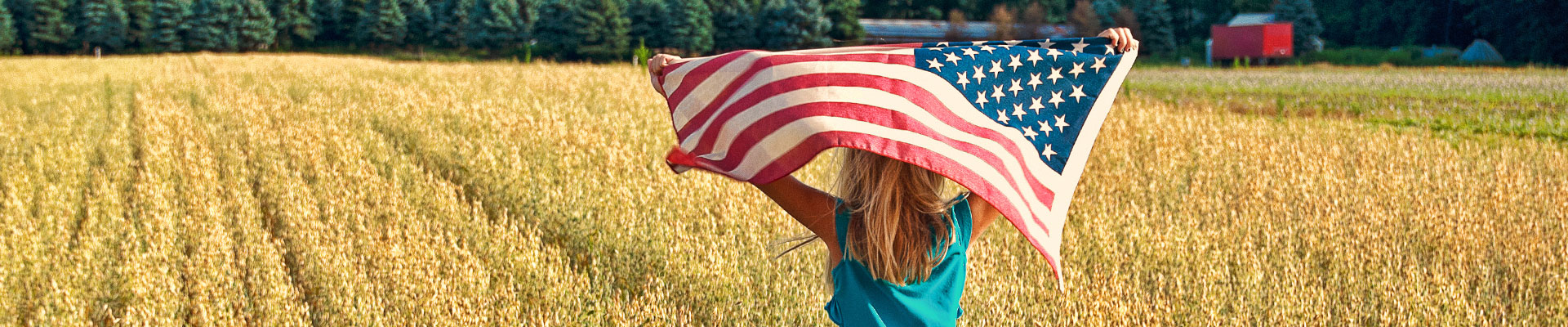 Young child walking through a field with the American Flag raised in the air.