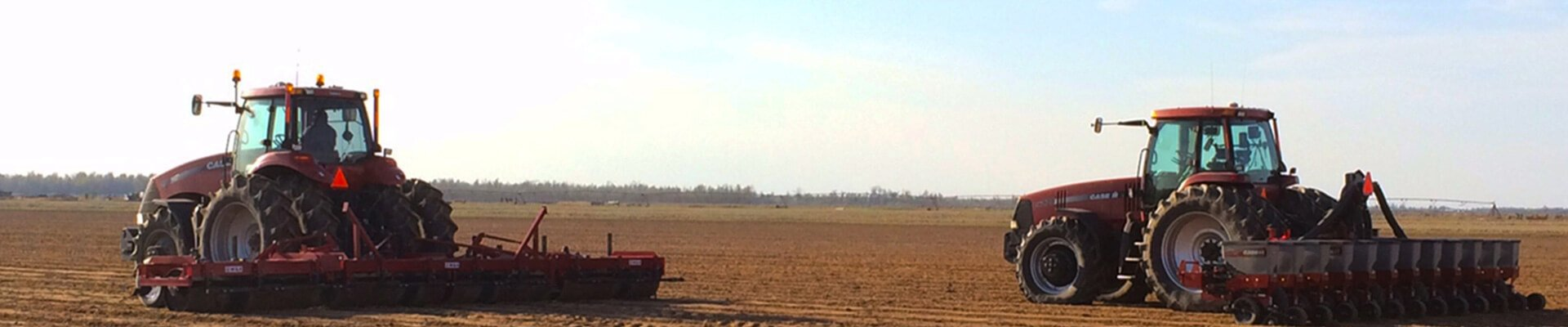 Two tractors working dirt in a field.