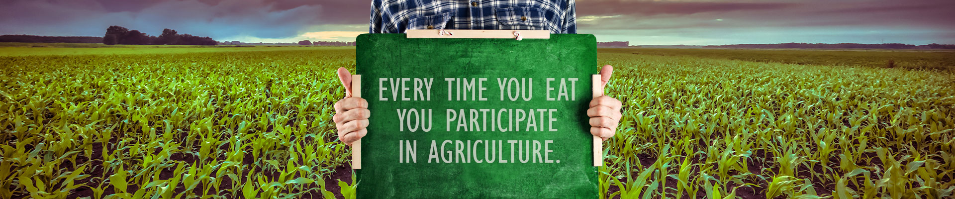Person holding a sign that says 'Every Time You Eat You Participate In Agriculture.'