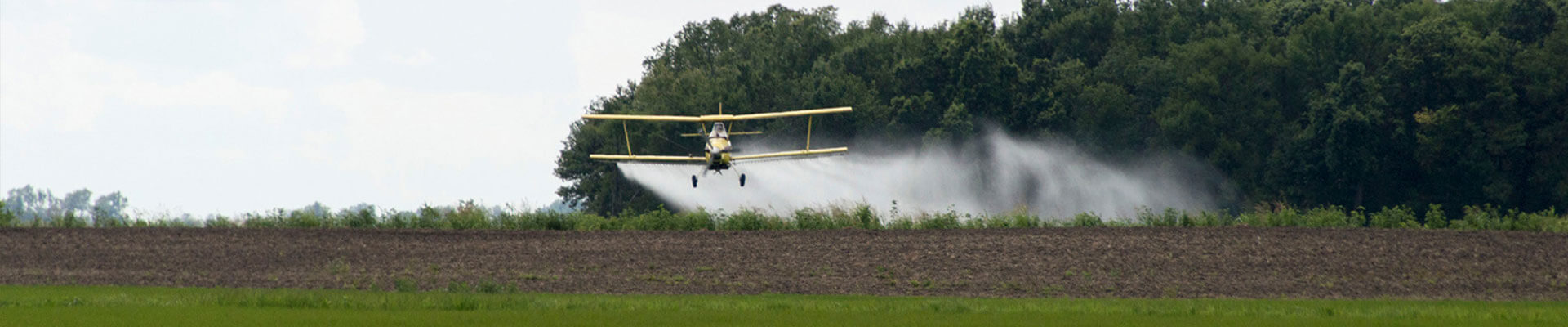 crop duster flying low over a field
