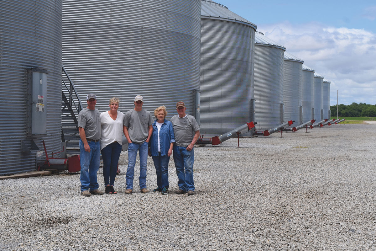 A family of farmers standing in front of a group of silos