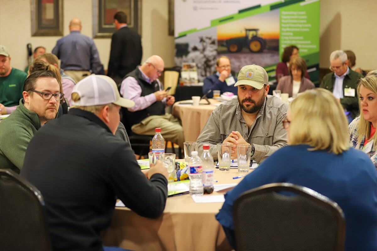 Farmers talking at their table during the YBS Conference